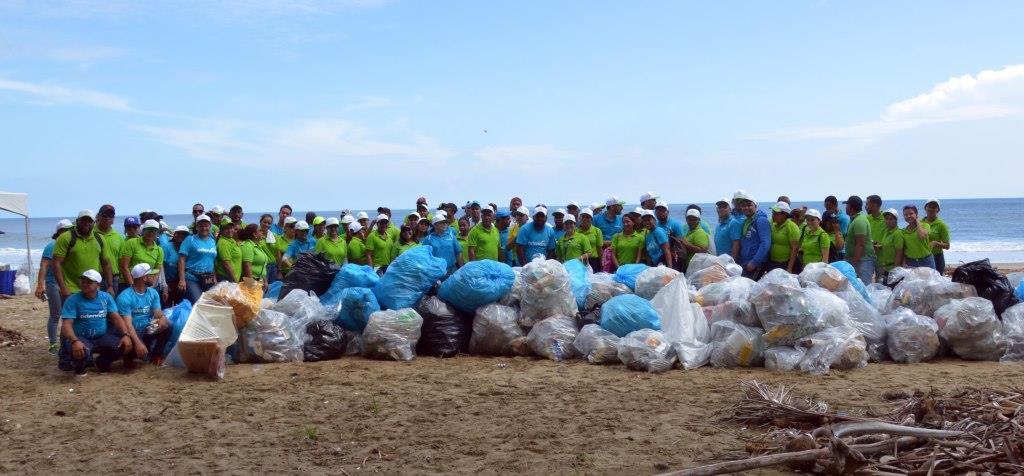 Al término de la faena, los voluntarios junto a los desperdicios retirados de la playa Matancita, del municipio de Nagua.